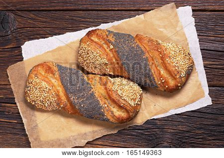 Buns with jam sesame and poppy seeds in plate on wooden table. Top view