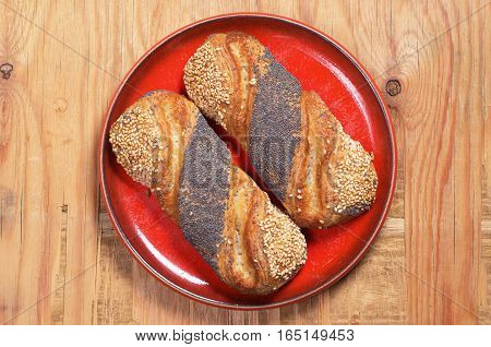 Buns with jam sesame and poppy seeds in red plate on old wooden background. Top view