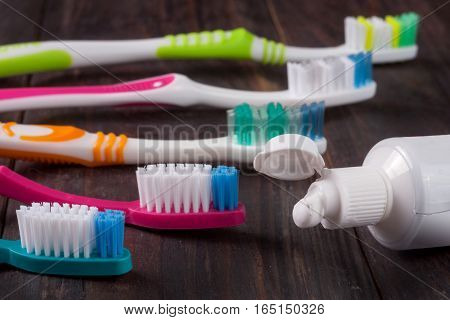 new manual toothbrushes on the dark wooden background.