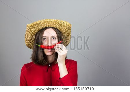 Girl in red with chili pepper as mustache. Young woman in traditional hat and red shirt posing with pepper holding it as mustache in front of studio background