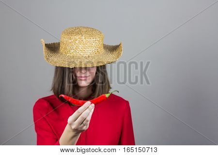 Girl in traditional hat and red blouse holds chili pepper. Young woman in red shirt and straw hat posing with a red pepper in front of grey background