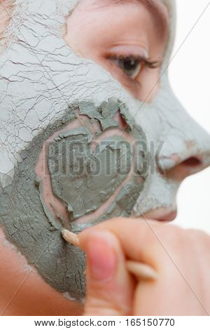 Woman having mud algae mask on her face smiling and making heart shape on her cheek