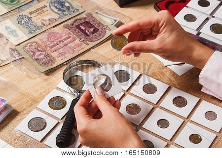 Woman Looks At The Old Coin