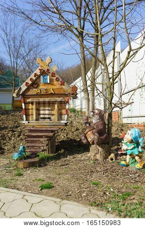 Decorated beehive and garden figures in the apiary. The words