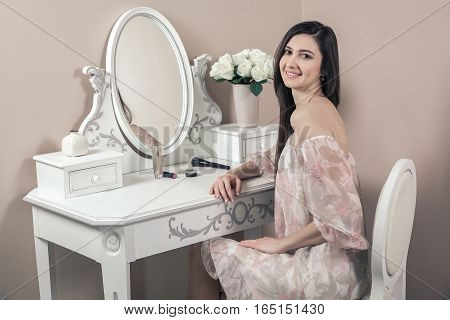 Beautiful happy woman with pink dress and long black hair in her room near her dressing table posing before party.