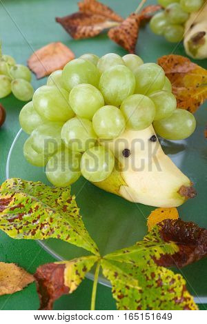 Funny food idea: fruit hedgehog from fresh pear and grapes.