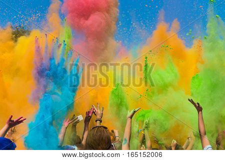 crowd of people throwing colored paint on Holi festival