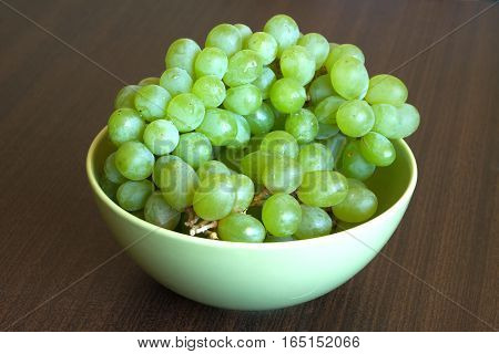 Grape in branch in green bowl on dark table surface close up