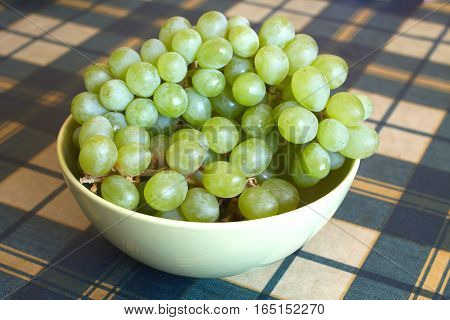 Still life with grapes on branch in green bowl on checkered tablecloth on table closeup