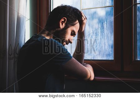 Young sad mad sitting by the window in regret