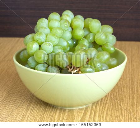Grape on branch in green bowl on sandy brown wooden table surface close up