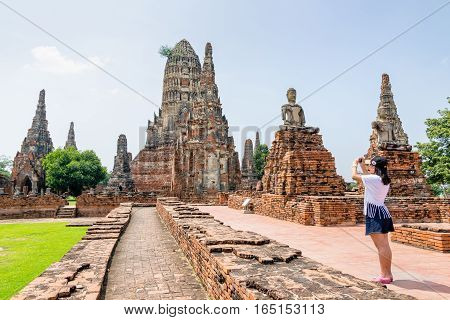 Tourist teenage girl take a photo ancient pagoda of Wat Chaiwatthanaram is buddhist temple famous tourist attraction religion at Ayutthaya Historical Park Phra Nakhon Si Ayutthaya Thailand