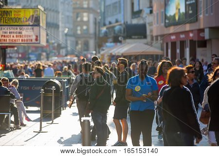 LONDON, UK - OCTOBER 4, 2015: Lots of people, tourists and Londoners walking via Leicester square, the famous destination for cinemas, restaurants and bars