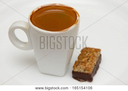 cup of hot espresso and candy on a white background, breakfast