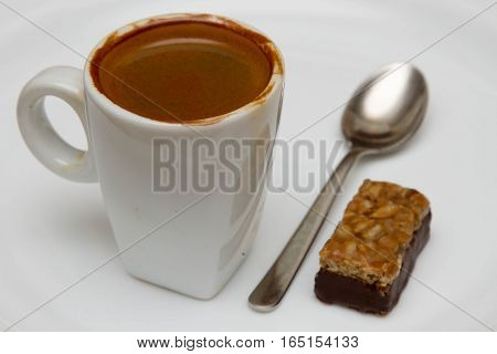 cup of hot espresso and candy on a white background,