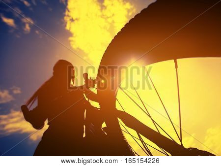 Silhouette of a cyclist riding a bike on the background of the cloudy sky. The concept of a healthy lifestyle and sports.