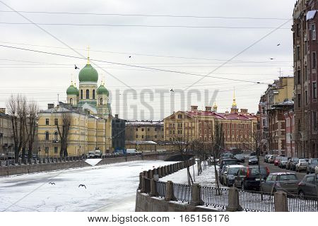 Orthodox Church architecture a 19th-century building on the embankment of Griboyedov canal Saint Petersburg flying ducks and doves winter street cars promenade urban landscape