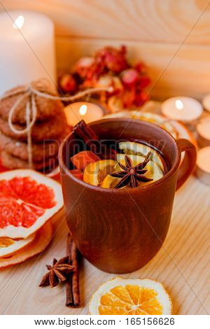 Tea with citrus in the ceramic brown cup. Dried citrus cookies and candles on the background