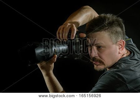 Portrait Photographer With A Camera On  Black Background