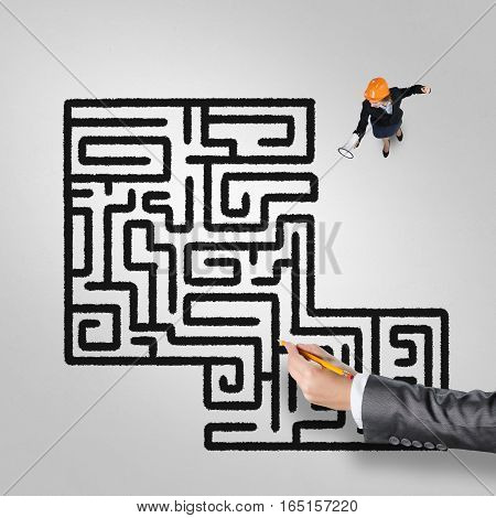 Top view of businesswoman with loudspeaker against maze drawn on floor