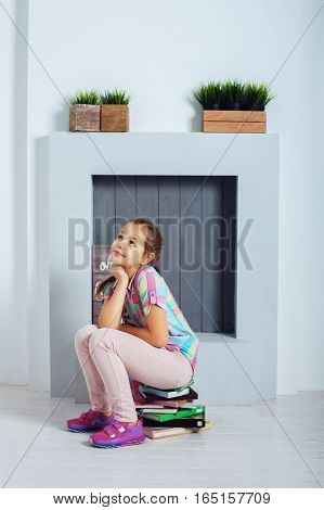 School girl sitting on a mountain of book. The concept of childhood training and education.