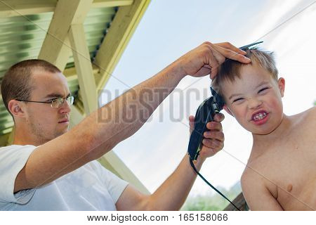 Big Brother Giving Little Brother With Downs-Syndrome a Haircut