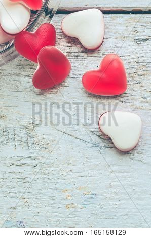 Red heart shape candy in a glass jar on a white rustic wooden table with space for text. Romantic love concept. Valentine's Day greetings card. Valentines theme. Top view. Copy space.