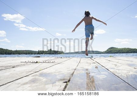 Pre Teen Boy Jumping Off Dock At Cottage