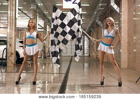 Full length shot of two hot leggy models at car wash service posing to camera with checkered race flag