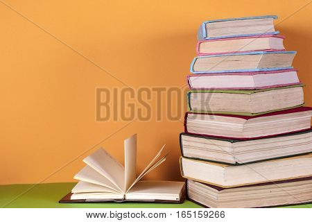 Open book hardback books on bright colorful background. Back to school. Copy space for text