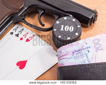 black pistol and a great poker hand of cards on a wooden background