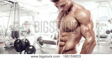 Muscular Bodybuilder Guy Standing On Gym