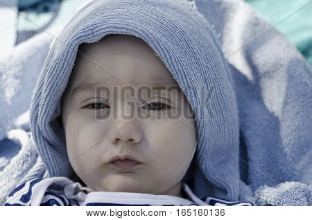 Cute baby face wrapped in towel with sparkling eyes