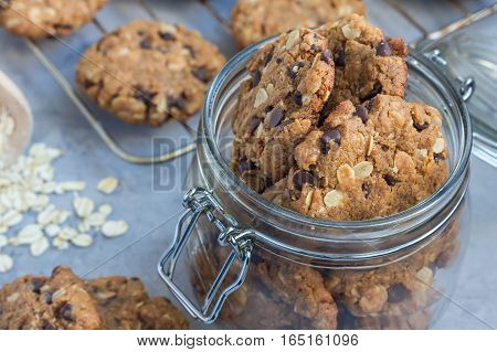 Flourless gluten free peanut butter oatmeal and chocolate chips cookies in glass jar and on table horizontal
