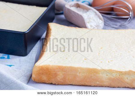 Homemade freshly baked square sponge cake ingredients on background horizontal