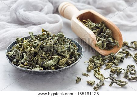 Dry green tea leaves on metal plate and on background horizontal