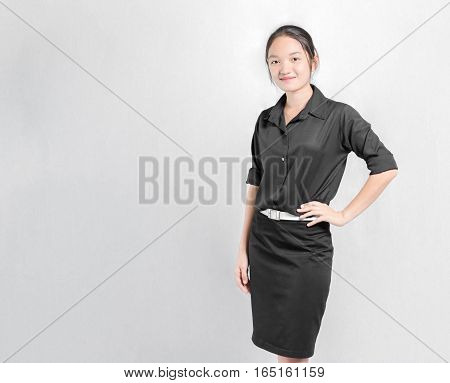 Portrait Of A Beautiful Asian Girl Akimbo In Black Uniform. Isolated On Grey Background