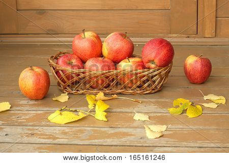 Autumn still life with ripe red apples in a wicker basket and yellow leaves scattered on a wooden surface painted brown