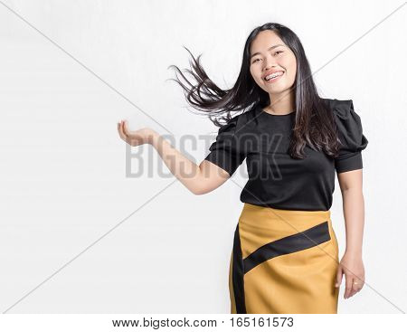 Portrait of a beautiful asian girl smiling and flicking her hair. Isolated on grey background with copy space