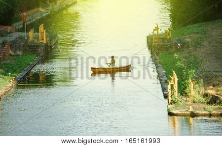 STRASBOURG FRANCE - AUG 5 2015: Man kayaking canoeing in Ill River next to European Parliament in Strasbourg on a warm summer day.