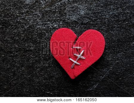 Red broken heart with thread stitches on dark background
