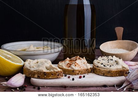 Sandwiches with hummus and few ingredients in rustic light.