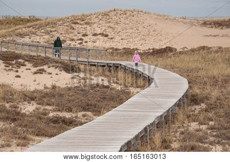 Wooden Walkway with Pink Raincoat thru Sand Dunes at Plum Island
