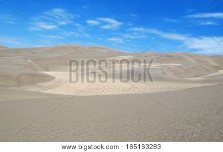 landscape of white sand dunes leading away to the horizon