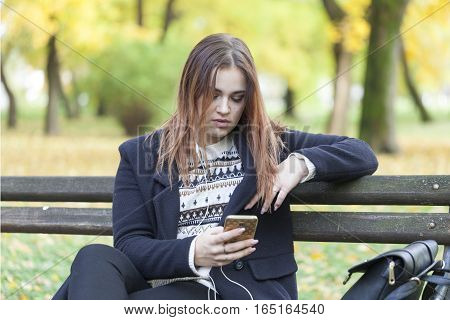 Young girl in a park on a bench listening to music Selective focus and small depth of field lens flare