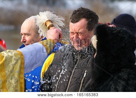 Rovzhi Ukraine - January 19 2014 Christian holiday Baptism in the Orthodox calendar. Father's hand with the aspergillum abundant sprinkles holy water man closed his eyes.