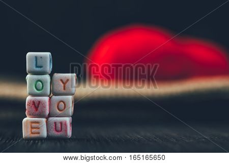 Word Love Written In Ceramic Blocks With Out Of Focus Heart In The Background