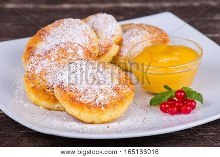 Cheese pancakes with honey in white plate. Close up