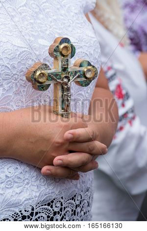 Old Ukrainian woman holding a Orthodox cross in the hands close up. Kiev Ukraine