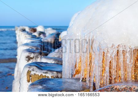 Icicles on an old breakwater on a sunny winter day